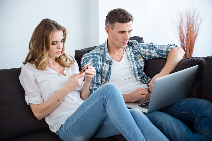 beautiful-couple-sitting-on-sofa-and-using-laptop-and-smartphone-separately_700 اگر به همسرمان شک کردیم چطور برخورد کنیم