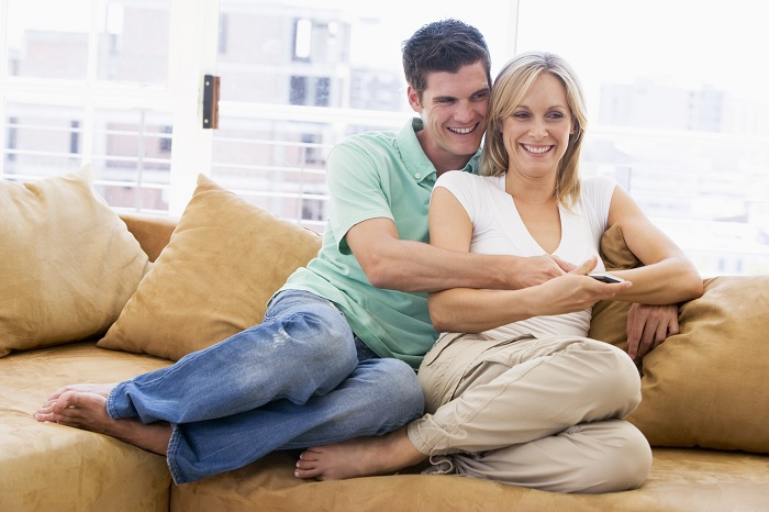 couple-in-living-room-with-remote-control-smiling_Ht_700 تا چه سنی می شود رابطه جنسی داشت