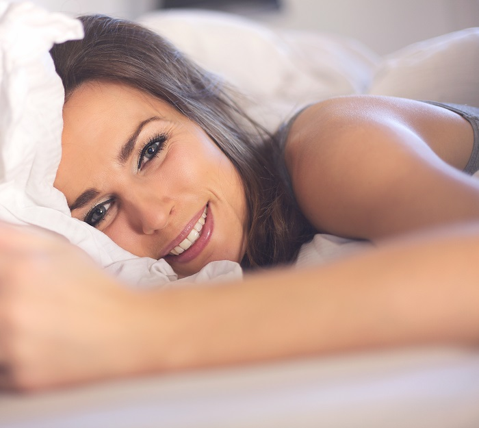 closeup-of-a-relaxed-woman-lying-on-bed-smiling_700 نقش لباس زیر زنانه در تحریک جنسی